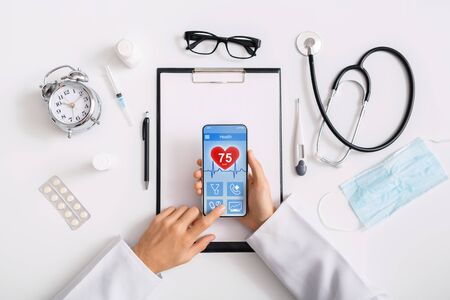 Modern medical application. Male doctor using smartphone with health rate information on screen at workplace, top view