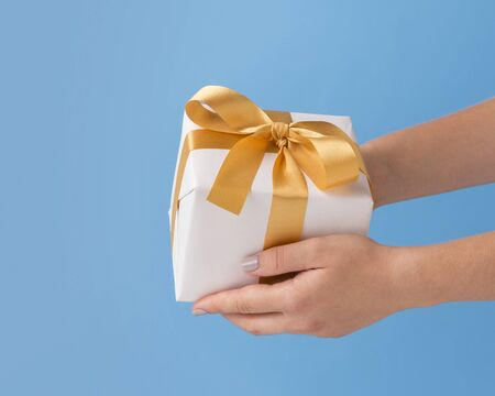 Time to giving presents. Woman holding New Year gift with gold ribbon over blue background, copy space Stock Photo