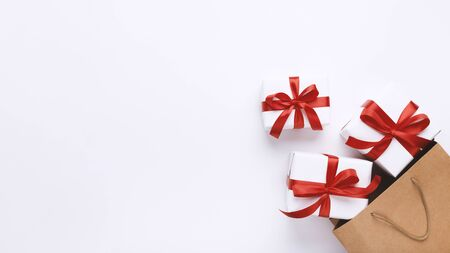 Christmas presents in beautiful boxes for winter holidays in shopping bag, white background, panorama, copy space