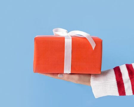 Close up Christmas present in box in woman hands over blue background