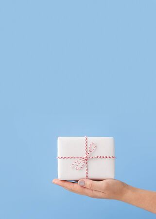 Hands holding small Christmas gift over blue background, copy space