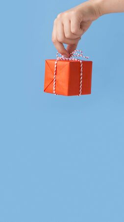 Celebrating Christmas. woman holding red box with gift over blue background, vertical panorama, copy space