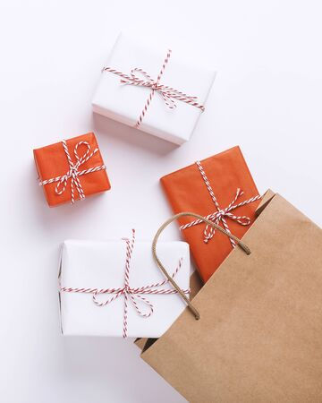 Christmas shopping concept. Wrapped gift boxes inside paper bag on white background