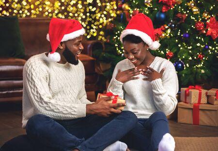 Loving black guy surprising his girlfriend with Christmas gift, sitting on floor near Xmas tree