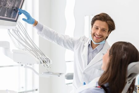 Handsome cheerful dentist doctor explaining his patient x-ray results, copy space 版權商用圖片