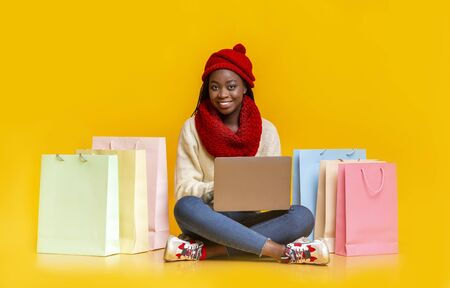 Happy black girl in warm clothes with laptop on her knees sitting among shopping bags, season of big discounts, copy space