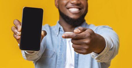 Unrecognizable afro guy holding smartphone with black screen and pointing on it, selective focus on hands with phone, panorama Stock Photo