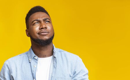 Portrait of suspicious black guy looking upwards at copy space on yellow background.
