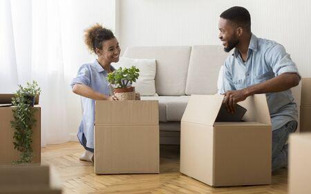Mudanza de apartamento. Feliz cónyuges negros embalar cosas en cajas de cartón sentado en el piso interior. Enfoque selectivo