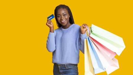 Happy young african american woman in warm blue sweater recommending credit card, holding shopping bags over yellow background, panorama with copy space