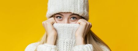 Close up of winter girl covering her nose and mouth with warm knitted sweater, panorama Stockfoto