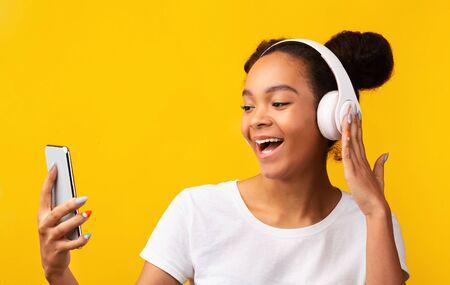 Alegre adolescente afroamericano escuchando música favorita con auriculares inalámbricos, fondo amarillo