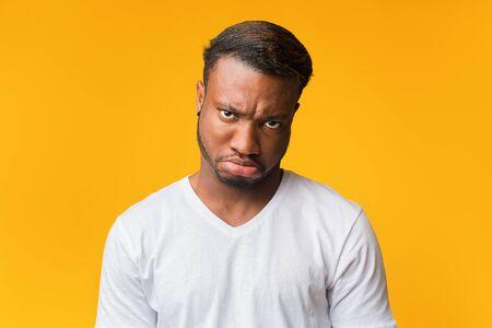 Grumpy Afro Guy Looking At Camera Posing Over Yellow Background. Studio Shot