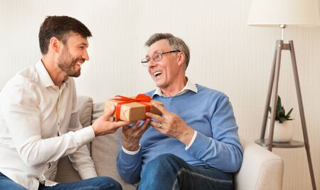 Mature Son Congratulating Elderly Father Giving Him Birthday Gift Sitting On Sofa At Home. Selective Focus