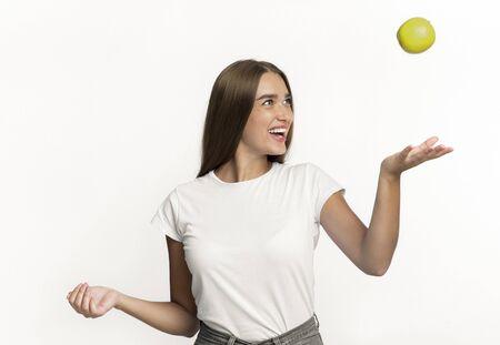 Fille heureuse jetant une pomme en l'air debout sur fond de studio blanc. Isolé