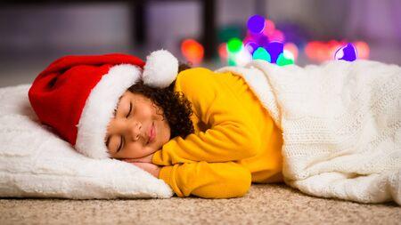 Adorable little african american little girl sleeping on floor on Christmas night, panorama Standard-Bild
