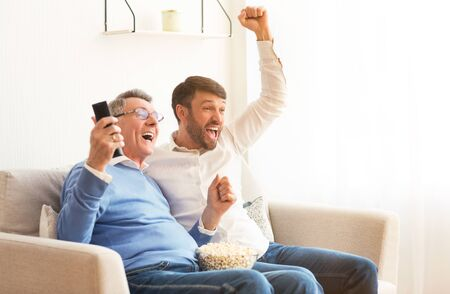 Excited Senior Father And Mature Son Watching Sport Match On TV Shouting Celebrating Victory Sitting On Sofa Indoor.