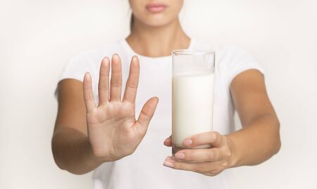 Lactose Intolerance Concept. Unrecognizable Woman Holding Milk And Gesturing No Standing In Studio On White Background. Cropped