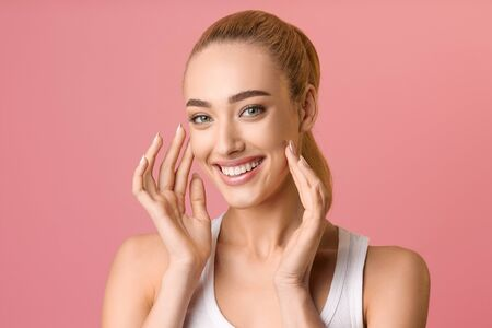 Woman with healthy skin touching her face and smiling to camera, pink background