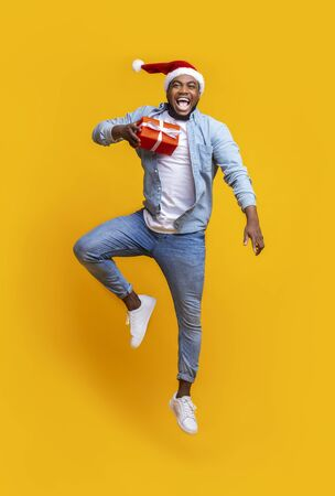 Positive young black guy with christmas present and santa hat jumping over yellow background, free space