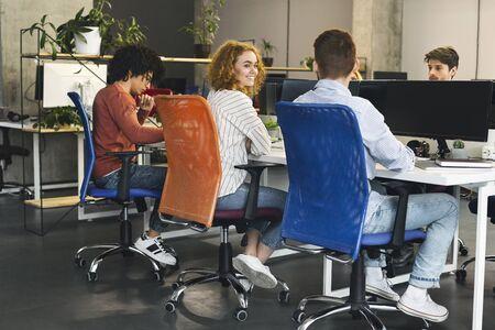 Grupo de jóvenes que trabajan en computadoras en la oficina Foto de archivo