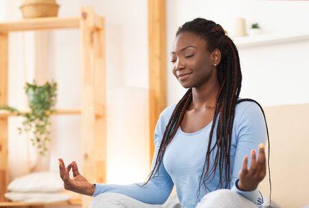 Friedliche Afroamerikanerin meditiert im Lotus-Yoga-Pose im Bett, die sich zu Hause entspannt. Selektiver Fokus