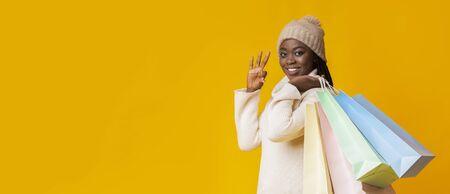 Feliz invierno niña africana con coloridas bolsas de la compra que muestran gesto bien, panorama con espacio de copia
