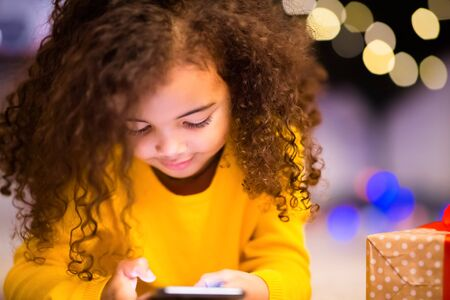 Cute little african girl playing with cell phone at Christmas eve, free space