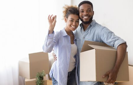 Happy Black Couple Showing Key Holding Moving Box And Hugging Standing In New Home.