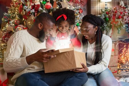 Excited african american family of three opening shining gift box in living room near Xmas tree, celebrating holidays at home
