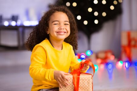 Happy Xmas childhood. Cheerful little black girl opening gifts on Christmas Eve
