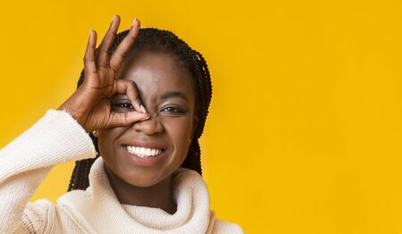 Portrait of positive afro girl in warm sweater covering one eye with okay gesture over yellow background, copy space