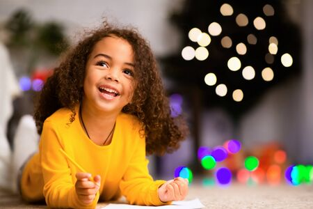Dreamy african child writing wishlist for Christmas holidays, empty space
