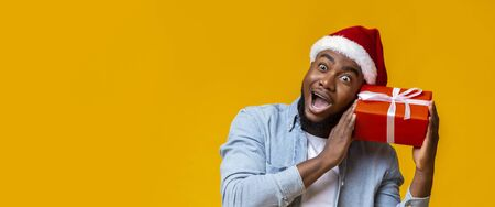 Funny african american guy holding Cristmas gift box and wonder whats inside, yellow background, panorama 版權商用圖片