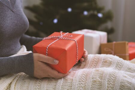 Girl holding her Christmas present in hands and sitting on the bed, blurred background, copy space Stock Photo