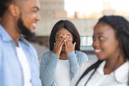 Desperate african american girl jealous to her dating friends, covering her face with hands, envy about their relations Stock Photo
