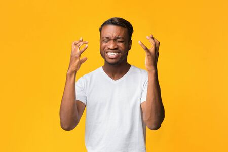 Frustrated Afro Man Gesturing With Hands Expressing Disappointment Standing Over Yellow Background. Studio Shot