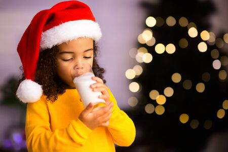 Little african american girl drinking warm milk near Christmas tree, copy space