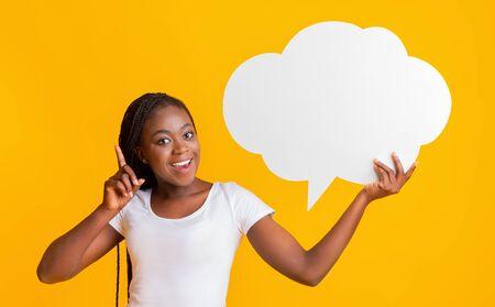 Aufgeregtes Afro-Mädchen, das Kommunikationsblase hält, mit dem Finger nach oben zeigt, eine gute Idee hat, gelber Hintergrund