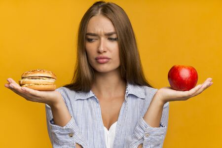 Puzzled Lady Holding Burger And Apple Choosing Between Unhealthy And Healthy Food Standing Over Yellow Background. Studio Shot