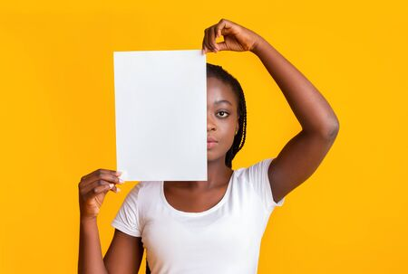 Serious afro girl covering half of her face with blank empty paper over yellow background Stok Fotoğraf
