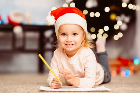 Funny toddler girl drawing wish list for Santa Claus, lying on floor at home, free space Stock Photo