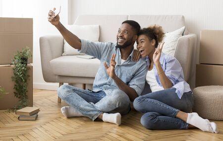 Pareja afro tomando Selfie con smartphone gesticulando signo de victoria después de mudarse a casa nueva. Copia espacio Foto de archivo