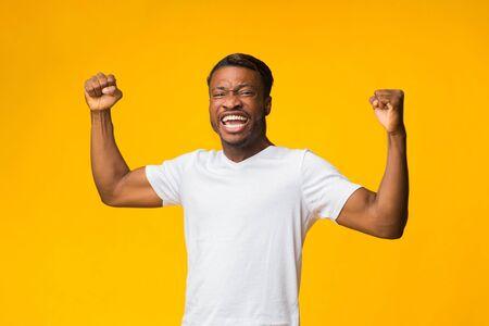 Emotional Afro Guy Shouting Shaking Fists Celebrating Success Standing On Yellow Background. Studio Shot