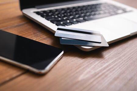 Smartphone avec écran blanc, ordinateur portable et cartes de crédit à plat sur une table en bois, gros plan
