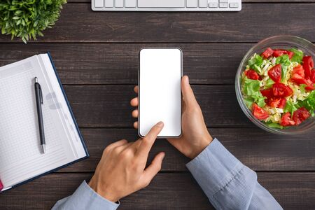 Man using smartphone with blank screen, counting calories of fresh vegetable salad, having healthy lunch at workplace, top view Stok Fotoğraf