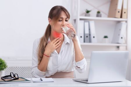 Sick Businesswoman Having Sore Throat Touching Red Pain Zone On Her Neck Holding Glass Of Water Sitting In Modern Office 免版税图像