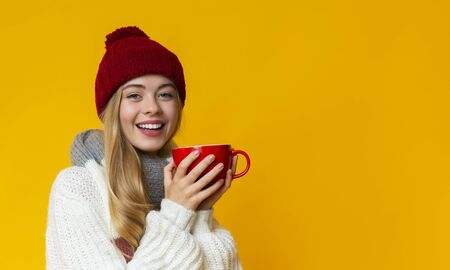 Portrait of pretty girl in winter hat holding red mug, panorama with copy space