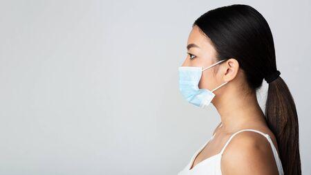 Chica asiática con máscara médica y mirando el espacio libre, fondo gris, vista lateral