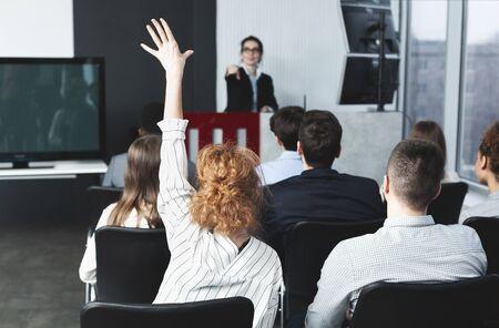 La empresaria levantando la mano en el seminario, orador femenino apuntando a mujer Foto de archivo